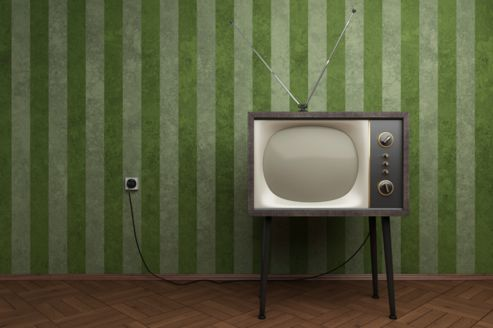 Old TV in empty room with green striped wallpapers